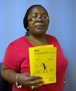 Linette holding a copy of the IM4Q monitoring document