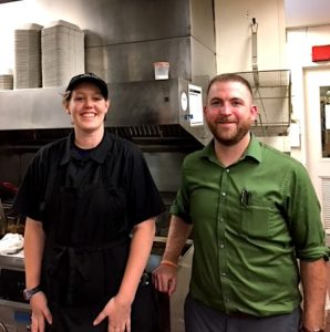 Picture of Lexi working in kitchen with her manager Travis